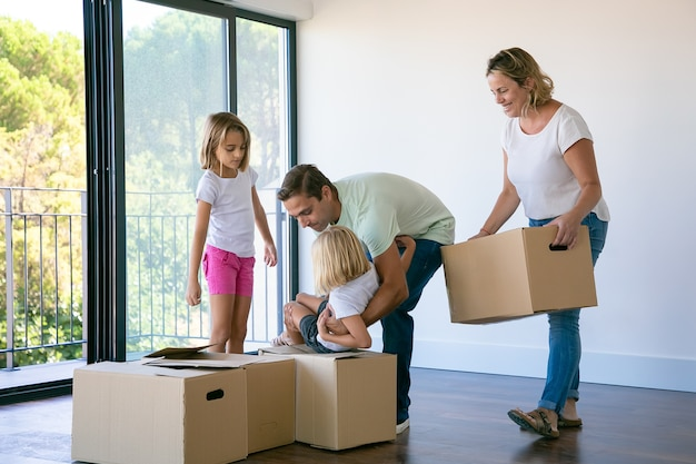 Happy family with kids near carton boxes standing in living room Free Photo