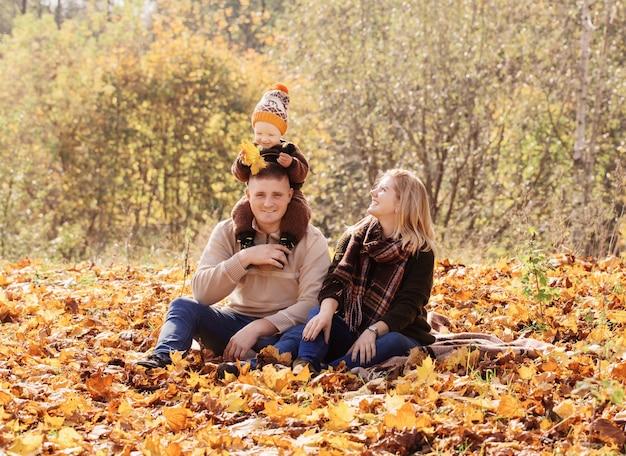 Счастливая семья с маленьким ребенком в осеннем парке Premium Фотографии