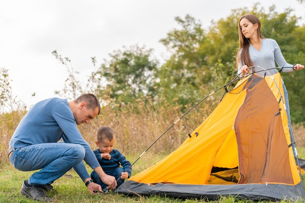 Happy family with little son set up camping tent. happy childhood, camping trip with parents. a child helps to set up a tent Premium Photo