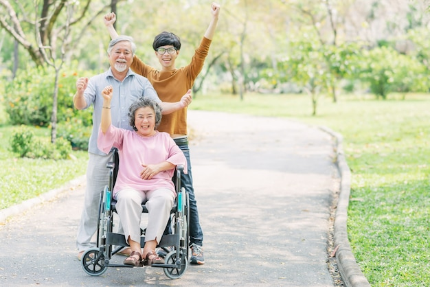 Happy family with senior woman in wheelchair in the park Premium Photo