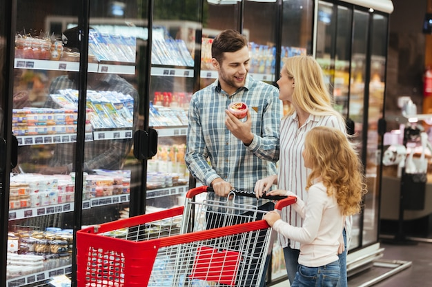Happy family with shopping cart in supermarket Free Photo