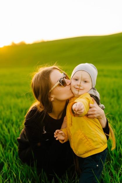 屋外で息子と幸せな家族。若い親は夏のフィールドで子供と一緒に歩く Premium写真