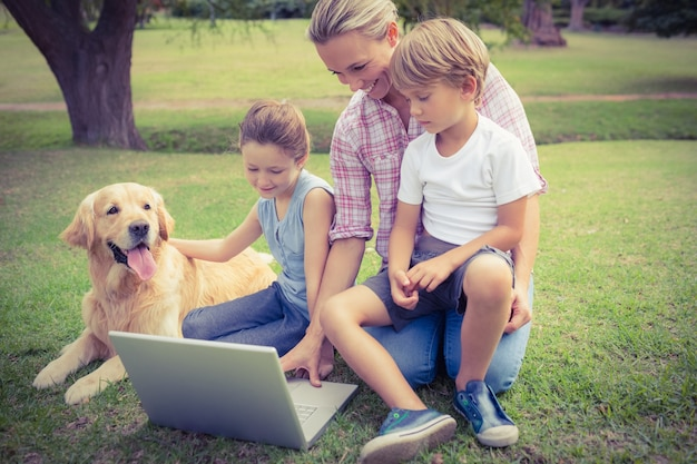 Happy family with their dog using laptop Premium Photo