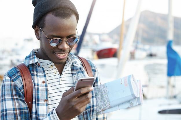Felice uomo dalla pelle scura alla moda che viaggia da solo in una località turistica europea portando una mappa cartacea sotto il braccio in cerca di caffè e ostelli nelle vicinanze usando una connessione internet 3g o 4g sul suo telefono cellulare Foto Gratuite
