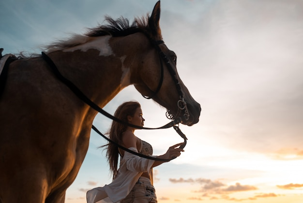 Happy fashionable young woman posing with a horse on the beach Premium Photo