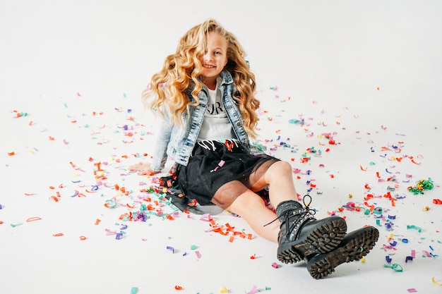Happy fashionably dressed curly hair tween girl in in a denim jacket and black tutu skirt and rough boots sitting on white  with colorful confetti Premium Photo