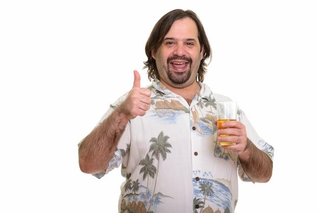 Счастливый толстый кавказский мужчина улыбается, показывая большой палец вверх и держа стакан пива, готовый к отпуску Premium Фотографии