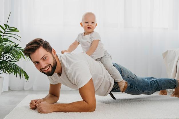 幸せな父と赤ちゃんが家で一緒に遊んでいます 無料写真