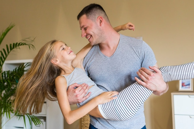 Счастливый отец и дочь играют в помещении Бесплатные Фотографии