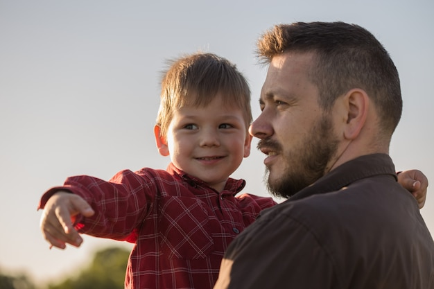 Счастливый отец и маленький сын отдыхают на поле ковыль Premium Фотографии