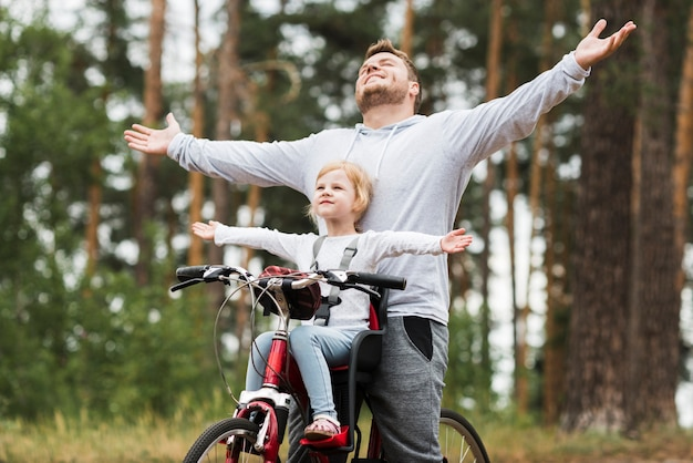 Happy father and daughter on bicycle Free Photo