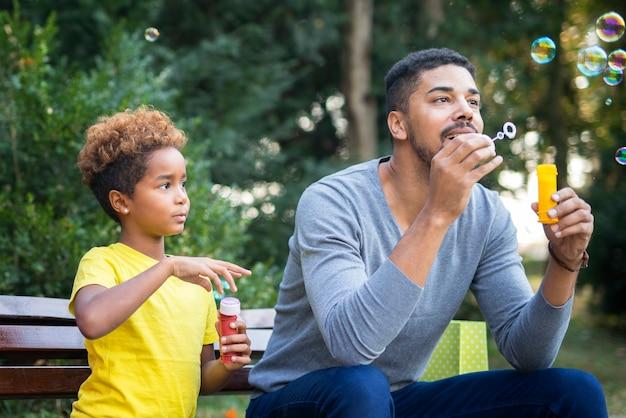 Felice padre e figlia che soffia bolle di sapone Foto Gratuite