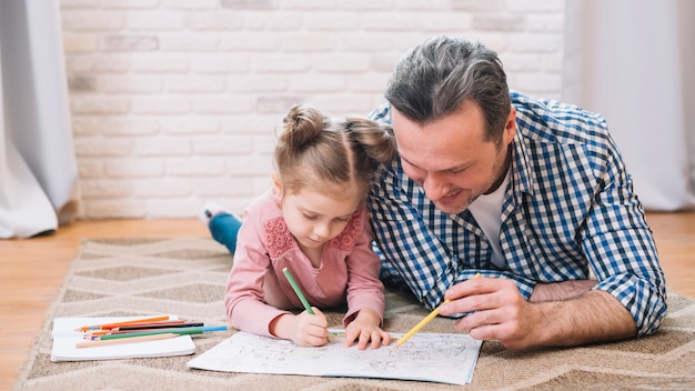 Happy father and daughter drawing together at home Free Photo