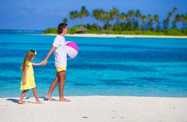 Happy father and daughter playing with ball outdoor on beach Premium Photo