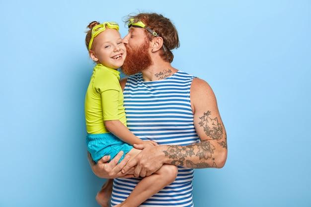 Felice padre e figlia indossano occhiali e vestiti estivi, si divertono insieme durante il riposo. papà affettuoso porta una piccola ragazza, la bacia sulla guancia, esprime amore. famiglia e concetto di ricreazione Foto Gratuite