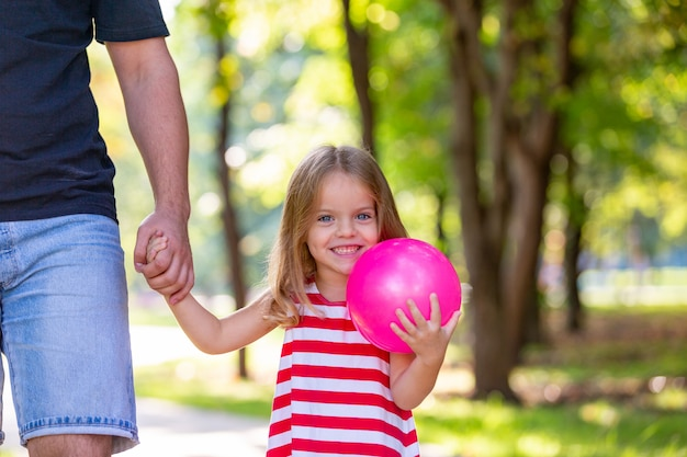 Happy father and little girl walking holding in hand in the summer park Premium Photo