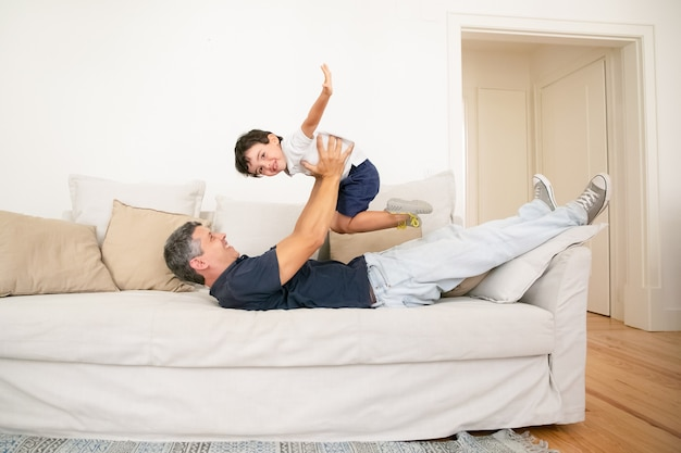 Happy father lying on sofa and playing with son. Free Photo