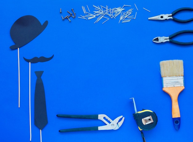 Happy father's day and tools colorful tie and hat on blue. Premium Photo