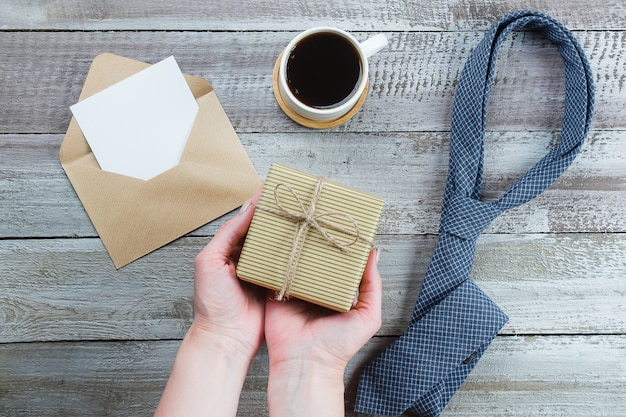 Happy father's day. woman hands holding gift or present box. blue tie, cup of coffee and empty blank Premium Photo