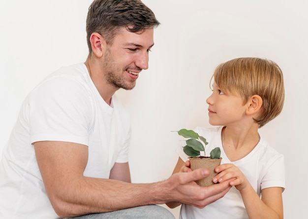 Happy father and son holding pot of plant Premium Photo