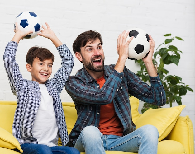 Happy father and son holding soccer balls Free Photo
