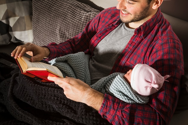 Happy father with baby reading book in evening Free Photo