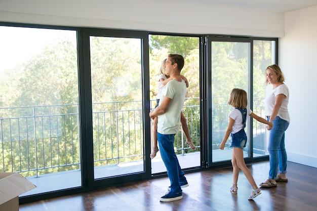 Счастливый отец с дочерью, стоя возле открытого балкона и улыбаясь Бесплатные Фотографии