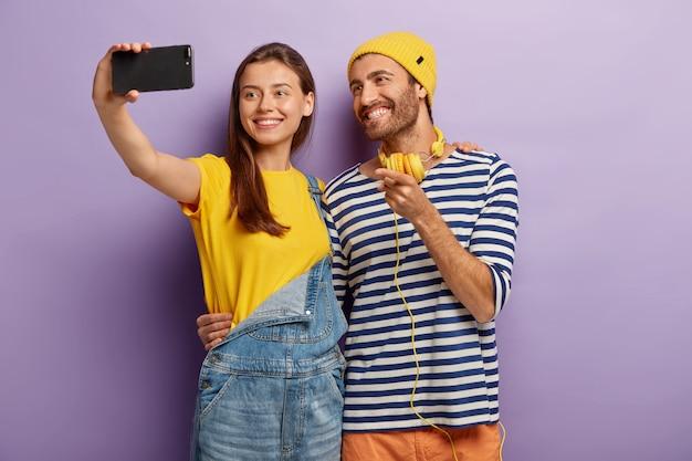 행복한 남녀 청소년들이 스마트 폰으로 셀카를 찍고, 미소를 지으며 포옹하고, 서로를 껴안고, 세련된 옷을 입고, 보라색 벽에 서서, 전시를 가리키고, 자신을 촬영합니다. 무료 사진