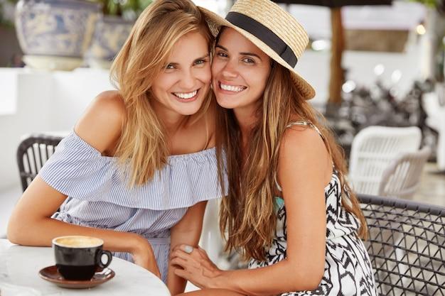 Happy female best friends sit at outdoor restaurant Free Photo