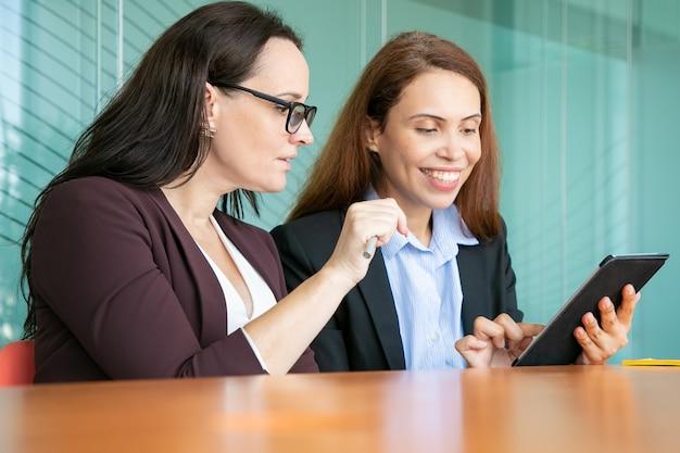 一緒にタブレットを使用して、画面を見て、会議室のテーブルに座って笑顔の幸せな女性ビジネス部門の同僚。 無料写真
