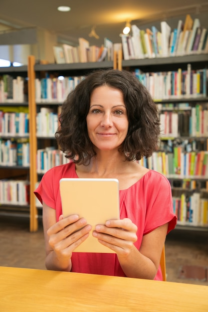 Happy female customer with gadget posing in public library Free Photo