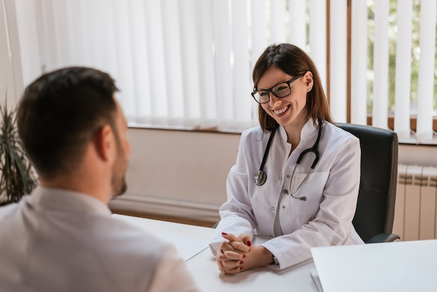 Happy female doctor discussing with patient at table in clinic Premium Photo