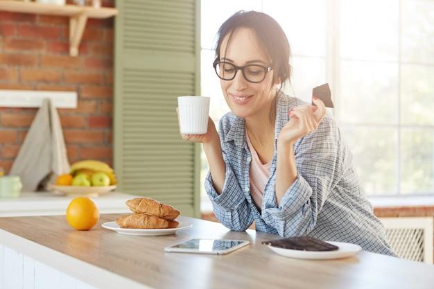 幸せな女性は甘いチョコレートを食べてお茶を飲み、タブレットで面白い映画を見て自宅で高速インターネット接続を使用しています 無料写真