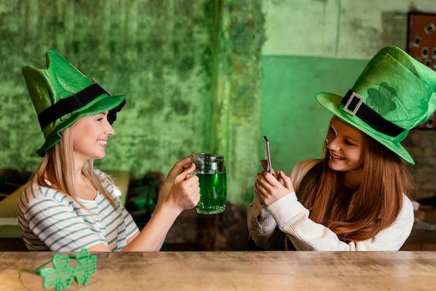 세인트를 축 하하는 행복 한 여자 친구. 술집에서 함께 패트릭의 날 무료 사진