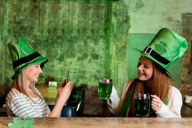 세인트를 축 하하는 행복 한 여자 친구. 음료 및 스마트 폰과 함께하는 패트릭의 날 무료 사진