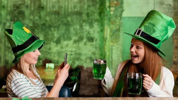 세인트를 축 하하는 행복 한 여자 친구. 패트릭의 날과 스마트 폰 및 음료 무료 사진