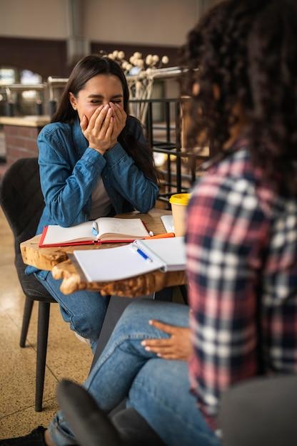 Счастливые подруги вместе делают домашнее задание в кафе Premium Фотографии