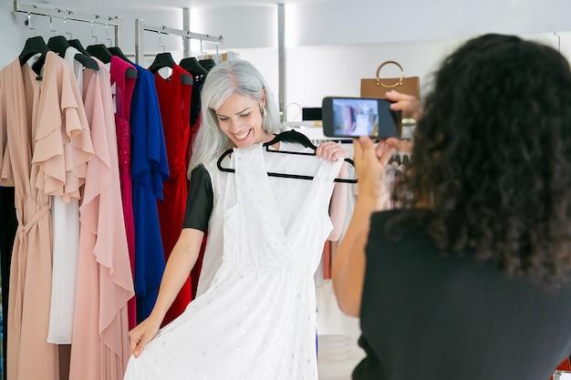 옷에서 쇼핑을 즐기고, 드레스를 들고, 포즈를 취하고, 휴대 전화로 사진을 찍는 행복한 여자 친구. 소비 또는 쇼핑 개념 무료 사진