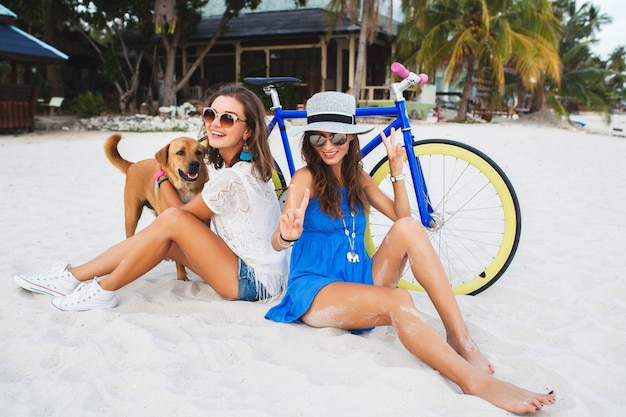 Happy female friends having fun on tropical beach, women traveling on vacation in thailand with bicycle Free Photo