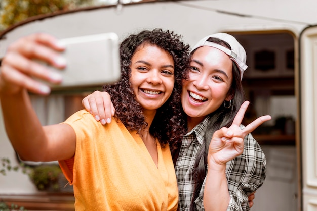 Happy female friends making the peace sign Free Photo