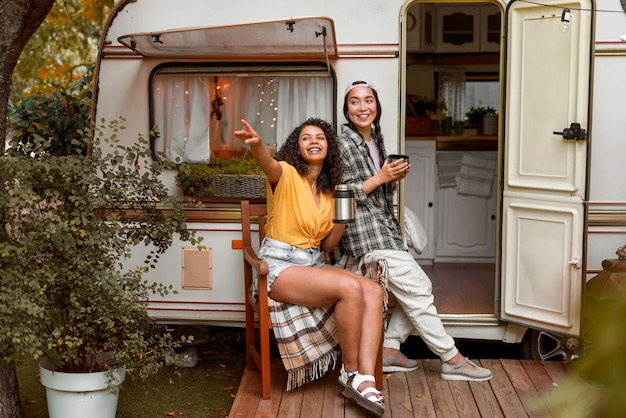 Happy female friends sitting next to a camper van Free Photo