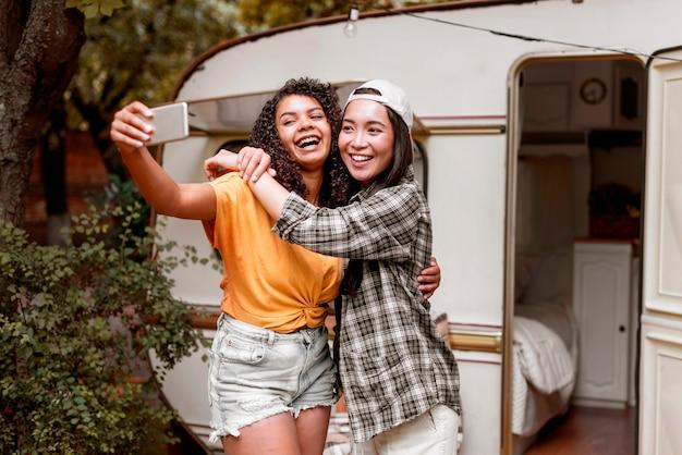 Счастливые подруги фотографируют на открытом воздухе Бесплатные Фотографии