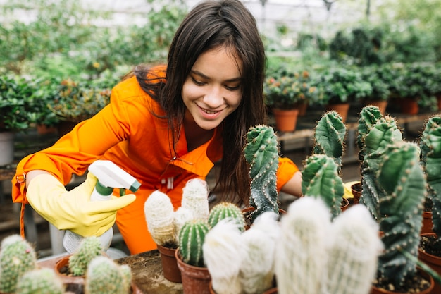 Happy female gardener spraying water on succulent plants Free Photo
