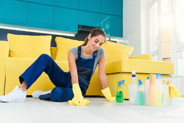 Happy female housekeeper mopping floor with detergents and rag in apartment. cleaning services concept. Premium Photo