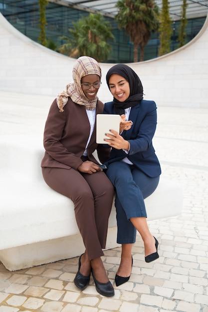タブレット上のコンテンツを見て幸せな女性オフィスの友人 無料写真