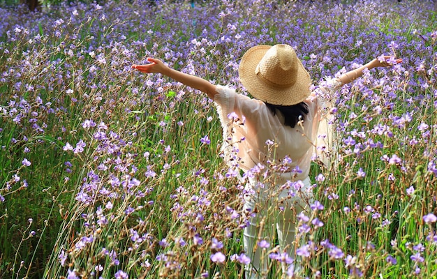 Happy female raising up her arms enjoy morning sunlight among the beautiful purple flower field Premium Photo