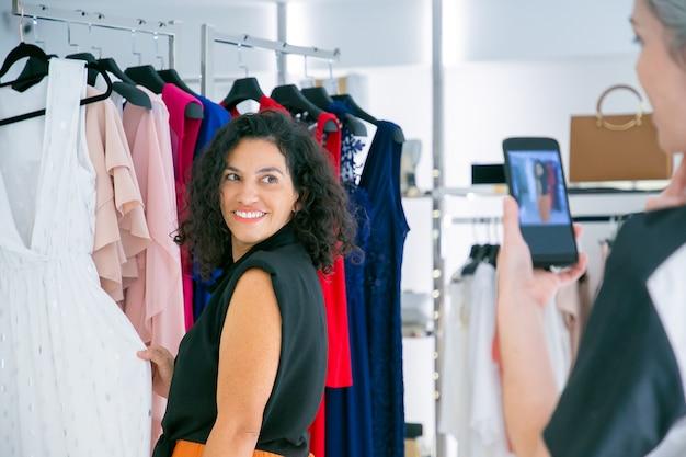 Счастливые покупательницы женского пола наслаждаются покупками в магазине одежды вместе, трогательно одеваются, позируют и фотографируют на мобильном телефоне. потребительство или концепция покупок Бесплатные Фотографии