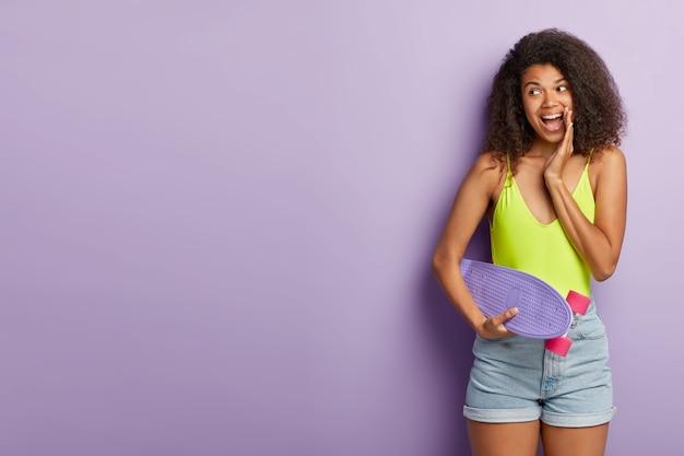 幸せな女性スケーターは娯楽中に好きな趣味を楽しんで、ロングボードを保持します 無料写真