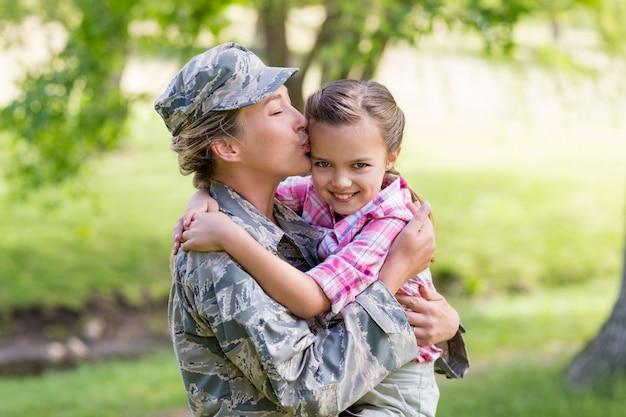公園で彼女の娘にキス幸せな女性兵士 Premium写真