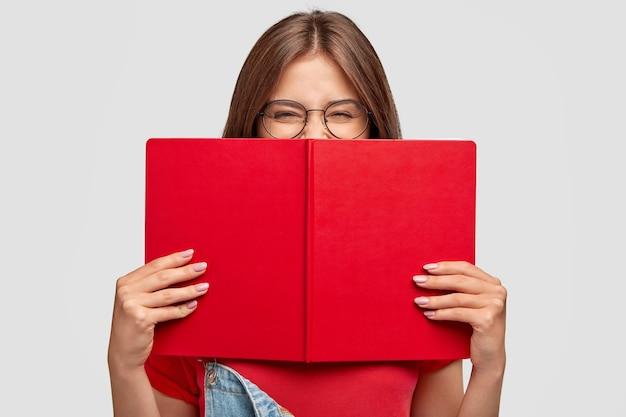 Счастливая студентка позитивно смеется, носит круглые очки, прячется за красную книгу, улыбается, читая что-то смешное, позирует у белой стены. люди, молодежь, образование и концепция чтения Бесплатные Фотографии